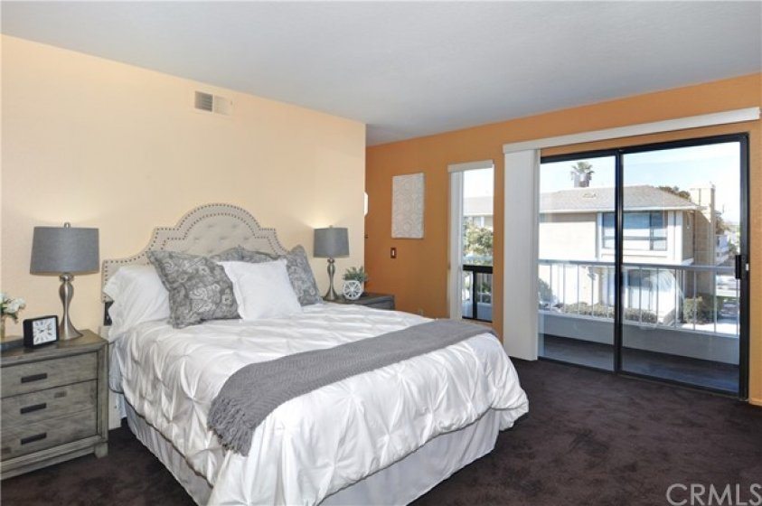 Large master bedroom at 2nd level of home with private balcony overlooking lake and community