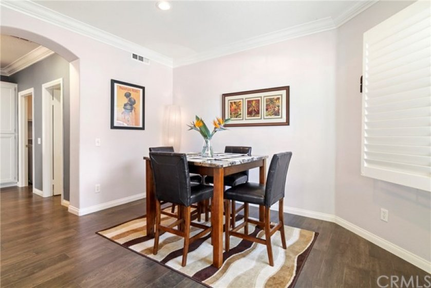 Light and bright dining area with crown molding and plantation shutters.