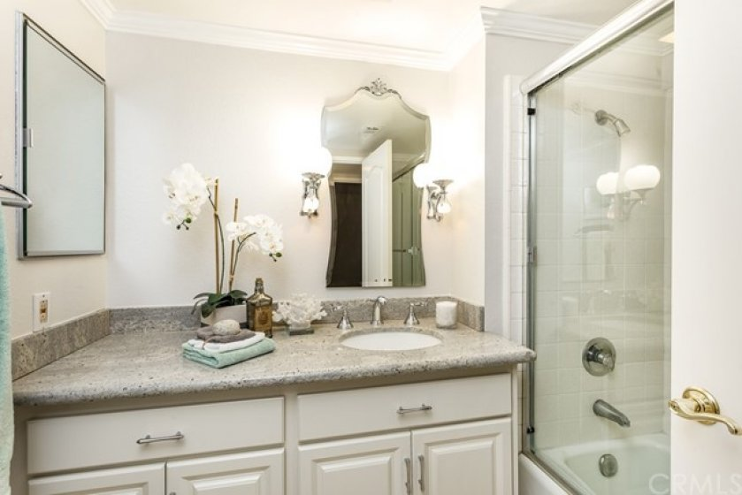 The guest bathroom has been beautifully updated with crisp white vanity, granite counters, designer lighting/mirror, and shower enclosure ... the crown moulding runs throughout the entire home as well