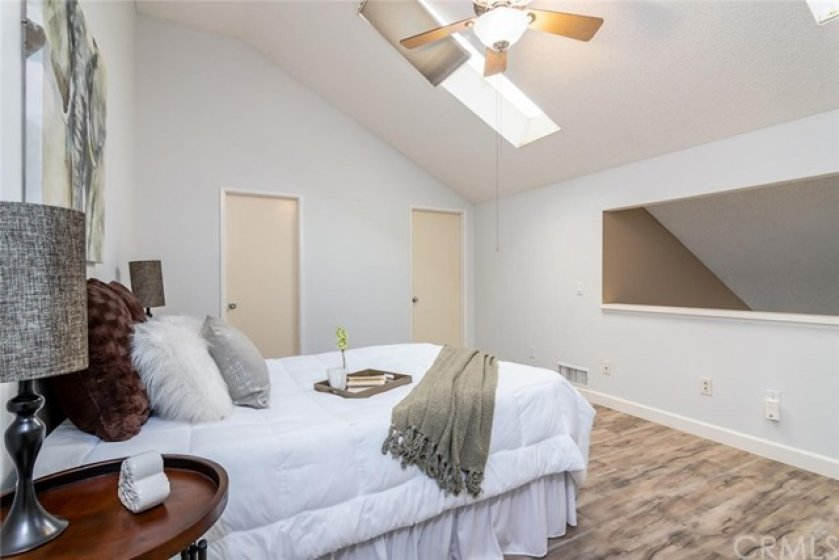 Upper floor loft/bedroom features: two opening skylights, ceiling fan, laminate flooring, walk-in closet and private half bath.