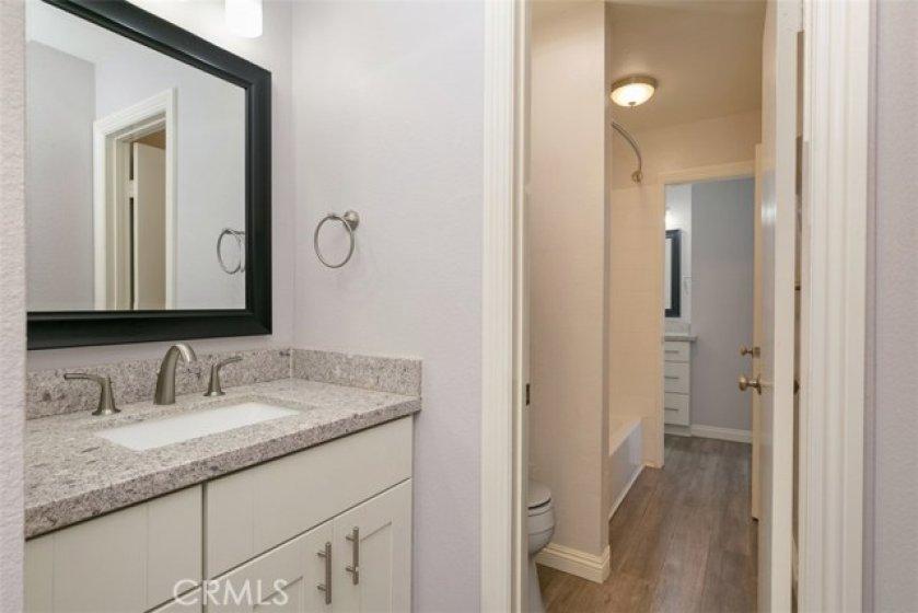 Hall remodeled vanity area, newer vanity, quartz counter tops, newer fixtures, mirror and light fixture
