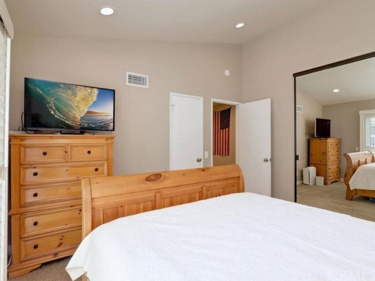 The upstairs master bedroom has recessed lighting, plantation shutters, and vaulted ceilings.