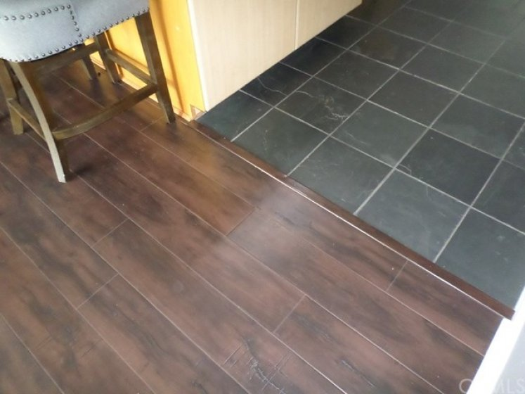 Upgraded laminate wood flooring in living room and bedroom installed by Seller - Slate flooring in Kitchen and entry.