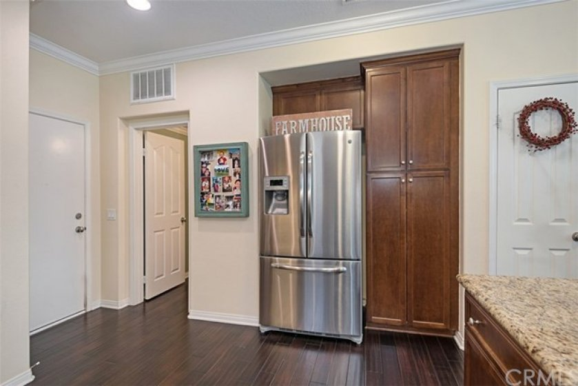 The kitchen has a stainless refrigerator, pantry, coat closet and is adjacent to the powder room