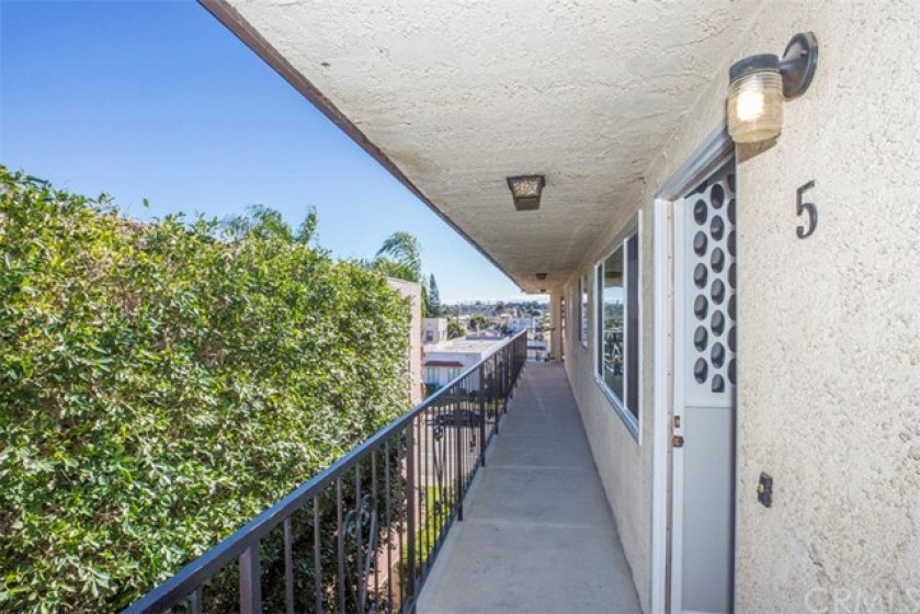Top floor, walk way to unit 5. (Lush shrubbery add privacy and ambiance to front of unit.)