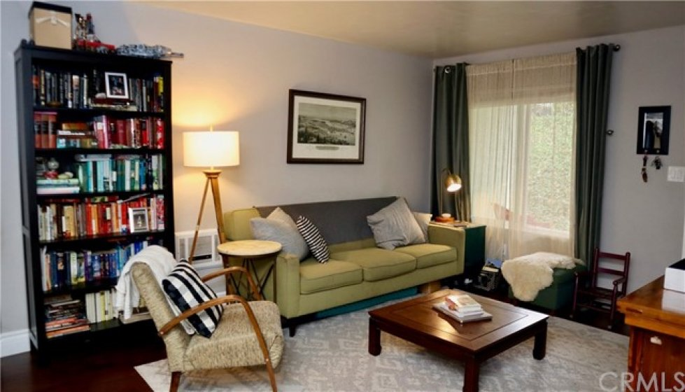 The spacious living room has attractive wood flooring and a feeling of openness.