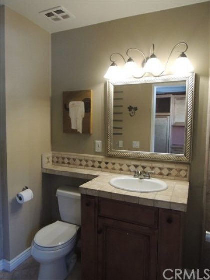 Updated half bath upstairs with newer vanity, tiled counter tops and backsplash, and updated mirror and lighting