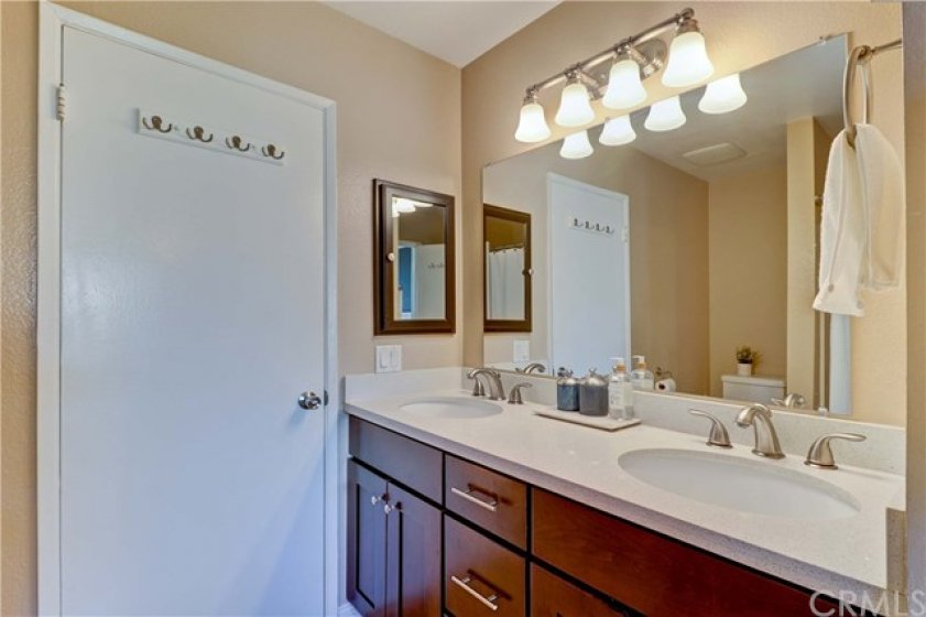 Upstairs bathroom is also updated to match the kitchen. Dual vanity. Quartz counters. Stylish lighting fixture. Bathtub.