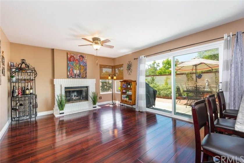 Family room features cozy fireplace accented with white brick, newer upgraded corner windows, newer patio slider, upgraded baseboards, newer paint, and upgraded ceiling fan.