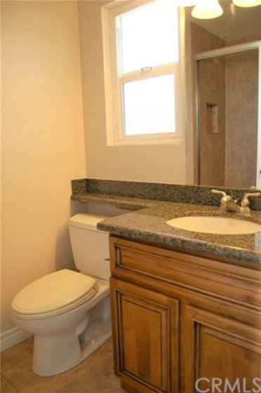 Powder bathroom on mid-level with upgraded fixtures and low-flow toilet.