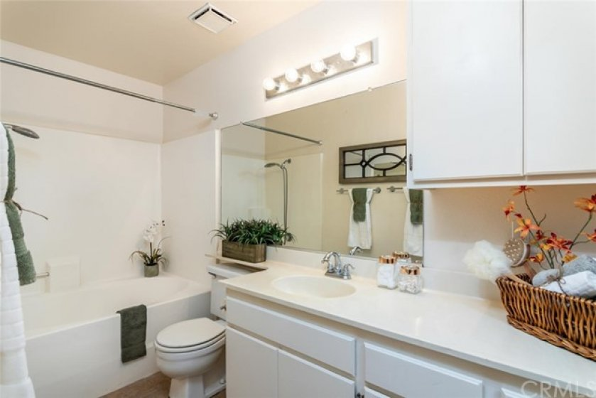Spacious bath bath with oval soaking tub, long vanity counter and lots of storage for linens and towels.