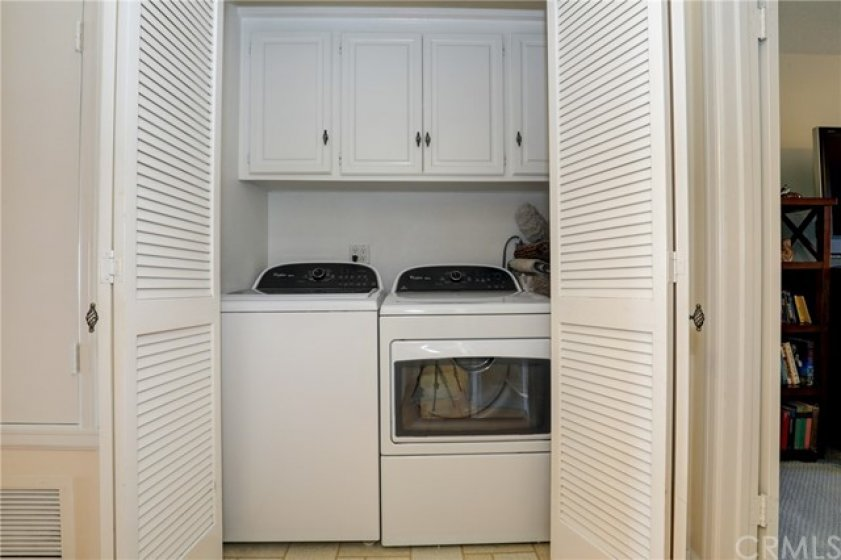 Laundry located next to the guest bedroom with cabinets
