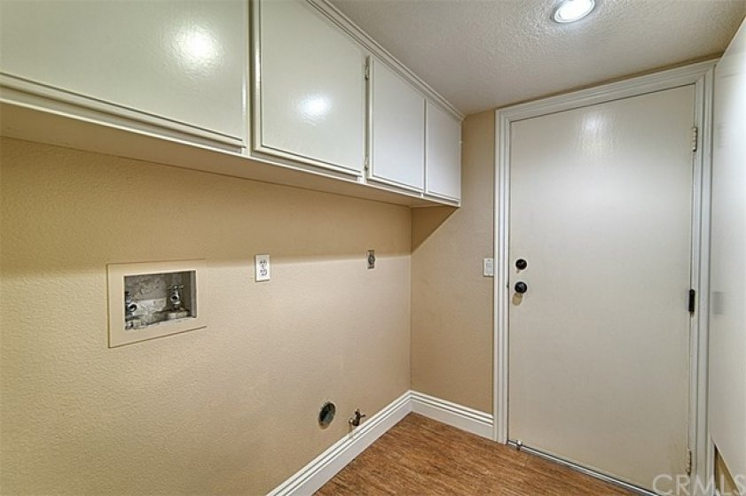 Laundry room has white storage cabinets and large white baseboards.