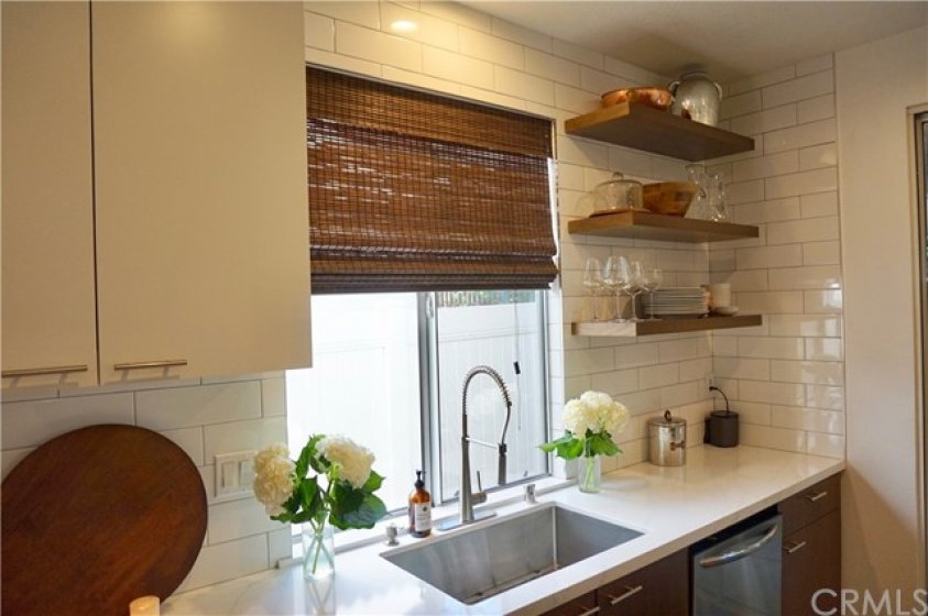 Commercial cabinetry and glass backsplash with stainless sink and dishwasher.