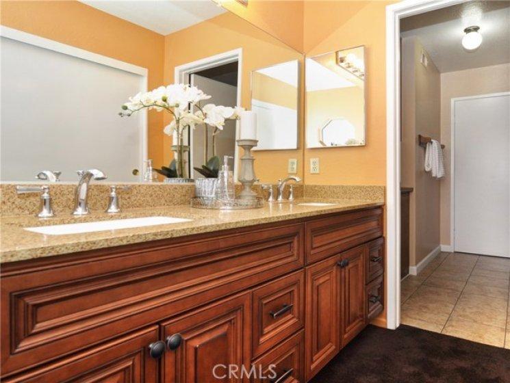 Upgraded master bath with dual vanities, raised panel doors, quartz countertop, carpet and tile flooring