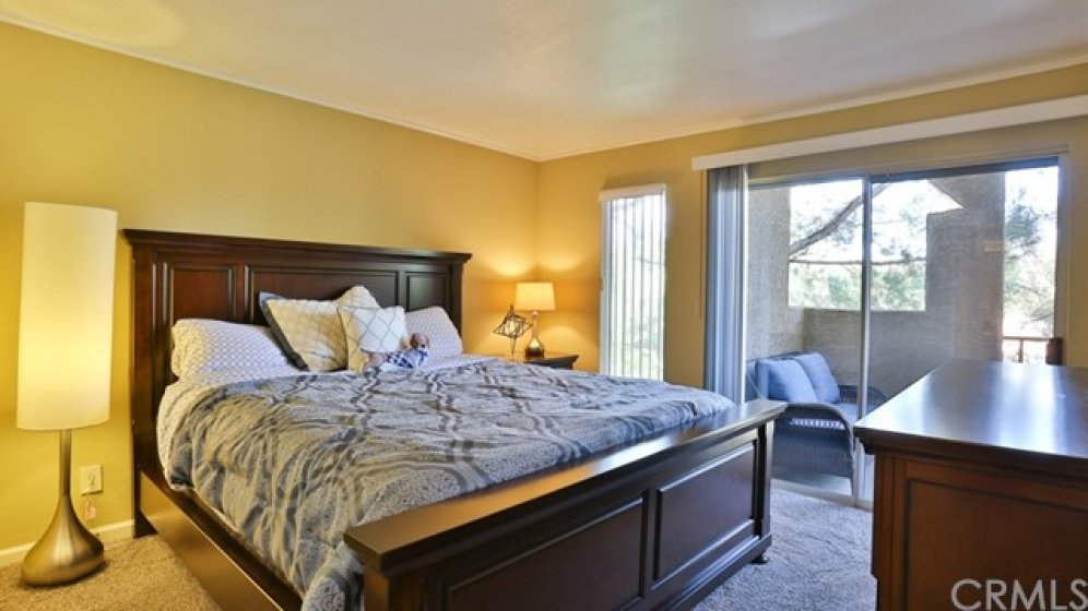 Bedroom is light and bright with sliding glass door to the balcony