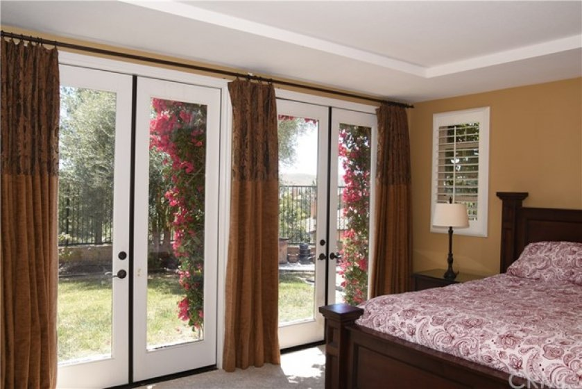 French doors from the master bedroom lead to the serenity of the uber private view yard.