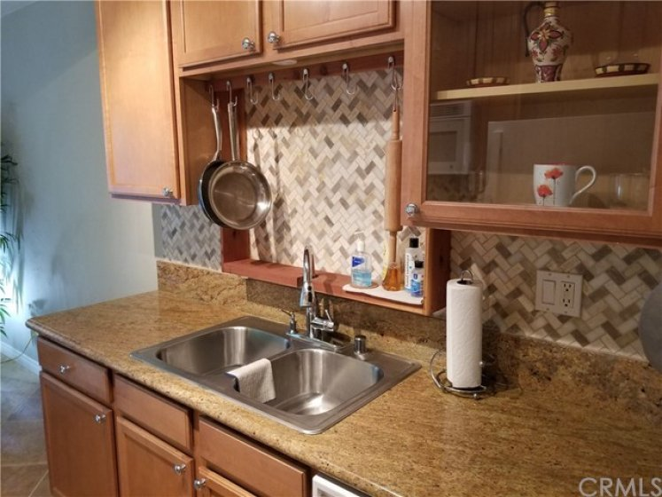 Natural wood upper and base cabinets.  Glass front upper cabinet.  Marble backsplash. Granite countertops. Stainless steel sink w/garbage disposal.  Chrome faucet w/sprayer.  Custom redwood hanging rack.
