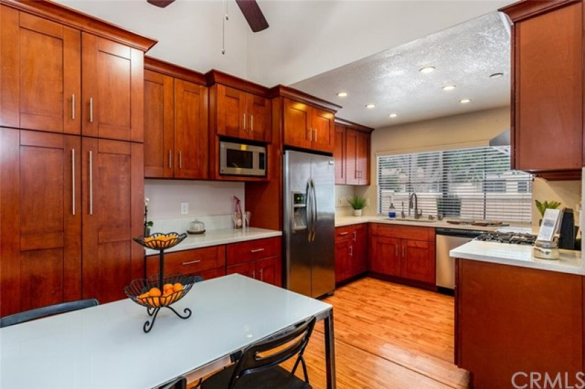Remodeled kitchen features wood Shaker style cabinets, double door pantry, quartz counters, stainless appliances and recessed lighting.