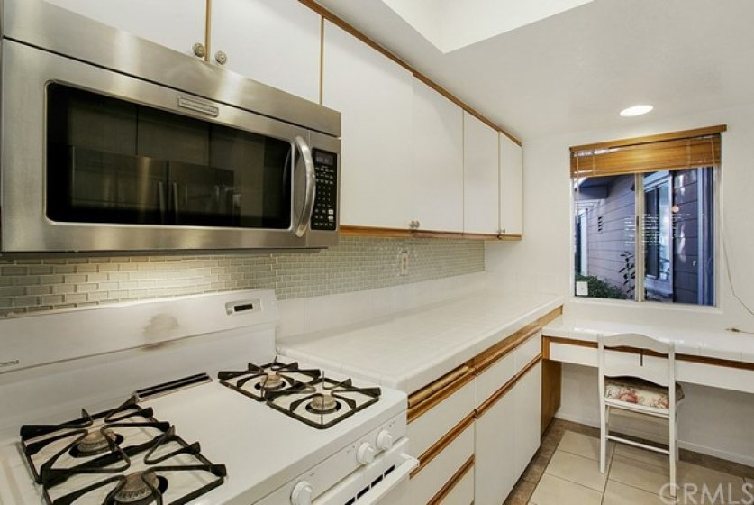 The kitchen comes complete with a gas range and built-in desk.