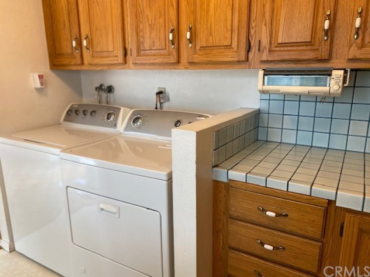 Washer and dryer included located in kitchen. Appliance under cabinet, older toaster oven.