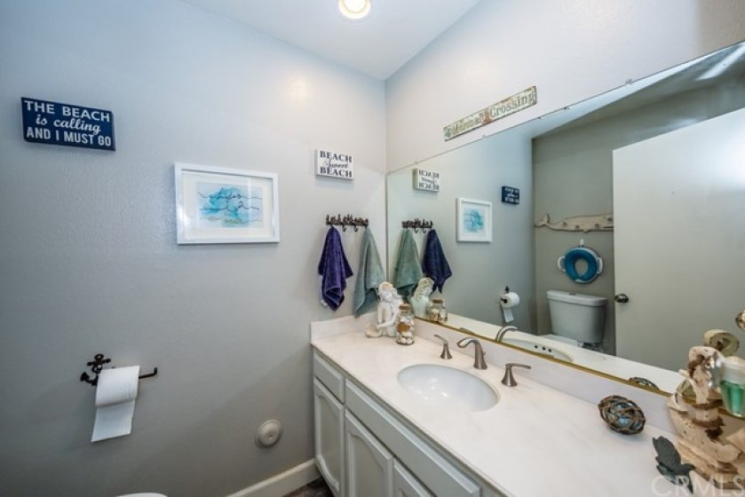 Downstairs half bath for guests has large vanity with sink and toilet.
