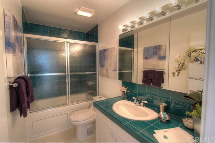 The updated bathroom has a Jacuzzi tub and shower combination with teal green ceramic tile.