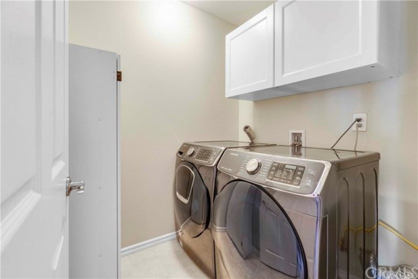 Enjoy the convenience of an upstairs laundry room with built-in cabinets.