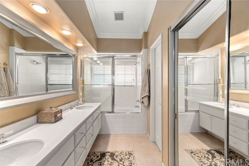 Master bathroom- Dual sinks large vanity counter- Glass closet door that enters into walk in closet with organizers-  Shower over tub with glass doors- Tile flooring