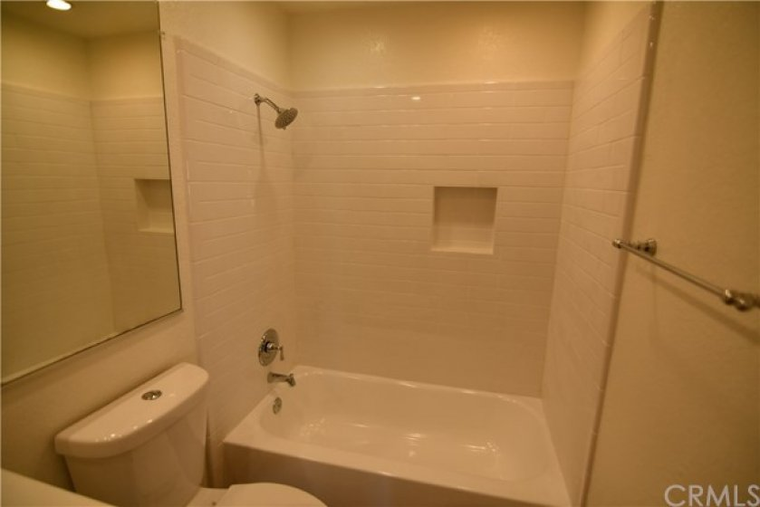 Here is a closer look at the new tile around your shower/tub, new tub/shower fixtures, refinished tub and new upgraded toilet. All freshly painted of course.