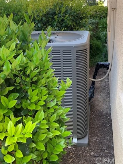 Newer Lenox AC condenser unit, located outside of the backyard and well hidden behind some hedges. No noise or wasted space in the back yard.