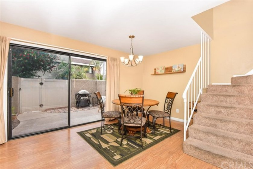 Family area shows partial stairwell and view of patio