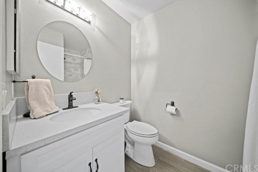 Main-level bathroom with updated vanity, mirror, light, hardware and beautiful walk-in shower with Carrara tile.