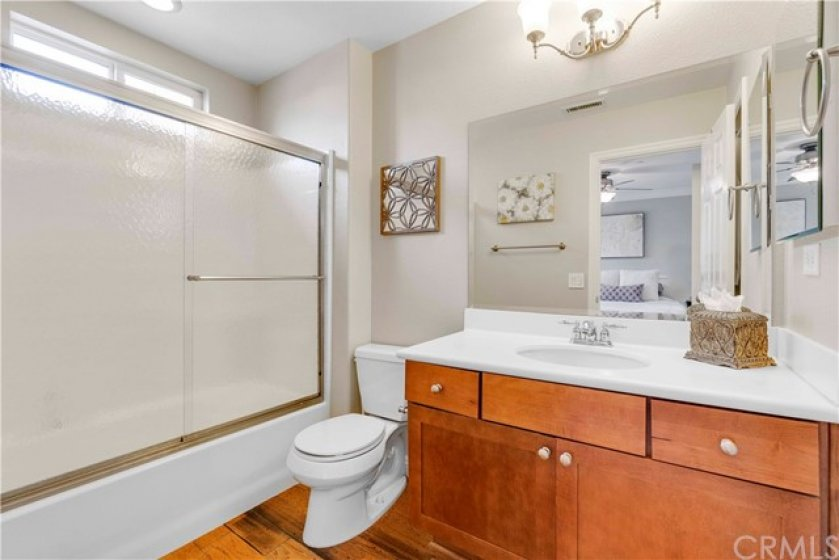 The back master suite features wood flooring, a walk-in shower with glass enclosure and dark shaker cabinetry.