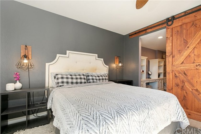Master bedroom with en-suite has newer floors, ceiling fan, walk-in closet, custom barn darn and access to backyard.