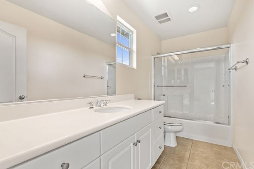 The top level en-suite bathroom features a shower/tub combination, large vanity and tons of cabinet space.