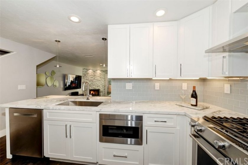 Remodeled kitchen with high end appliances, marble counters and glass tile backsplash.