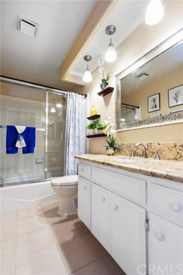 This is the hall bath shared by the secondary bedrooms. Pleanty of vanity storage, tile floor, tub/shower combination and framed vanity mirror