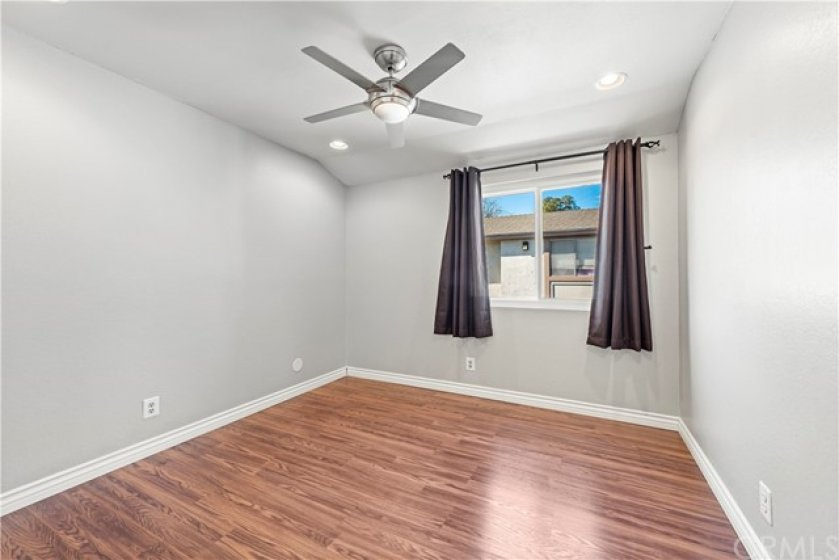 Secondary bedroom with ceiling fan and recessed lighting.