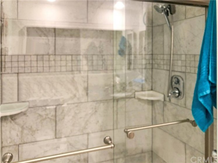 Tile shower with rain head and handheld shower fixtures