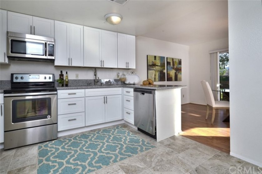 This gorgeous kitchen has been completely remodeled with crisp white shaker style cabinets and glistening granite counter tops.