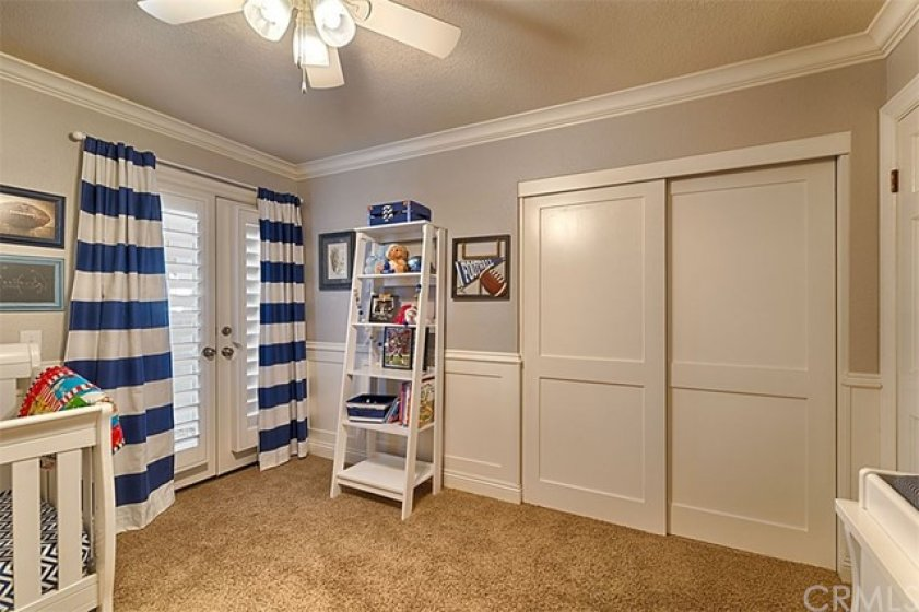 Secondary bedroom, large closet, ceiling fan, and French Doors to shared balcony.