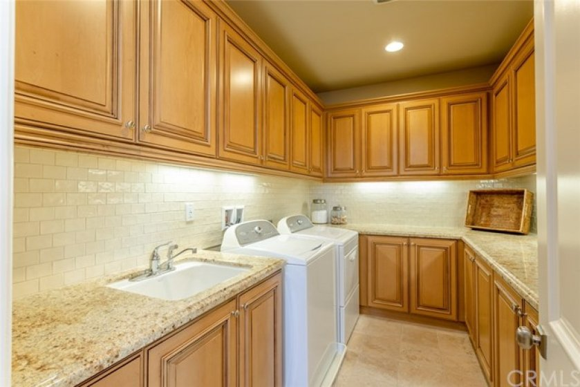 Separate laundry room with sink and washer/dryer hookups. Ample cabinets with Piedrafina counter top.