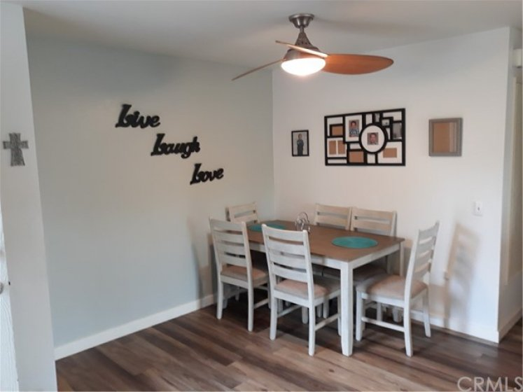 Dining room with ceiling fan and laminate hardwood floors.