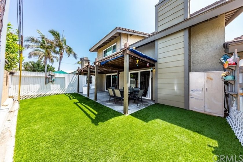 Enclosed patio with low maintenance artificial grass and concrete space for entertaining!