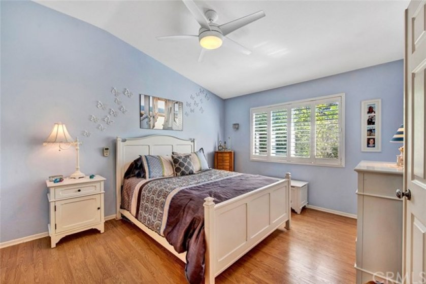 Spacious master bedroom with laminate wood flooring and plantation shutters on window