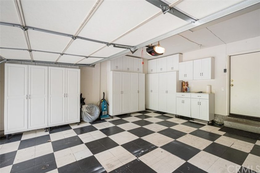 Two car attached garage with direct access, updated flooring, and cabinets.