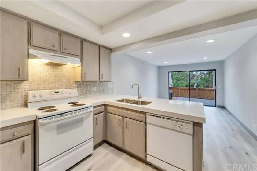 Kitchen and dining area overlooking patio with view of trees and woods.