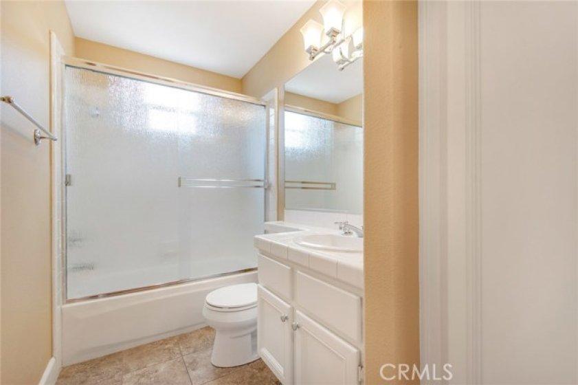 Main floor full bath with updated tile flooring, shower glass doors, fixtures, etc.