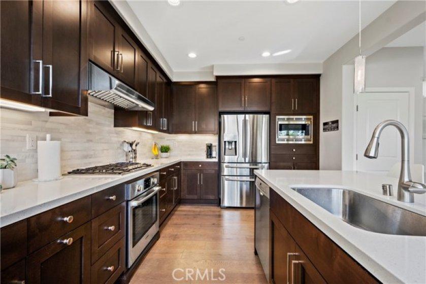 Gorgeous upgraded kitchen with full marble backsplash, pendant lighting & stainless steel appliances.